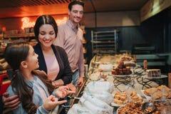 Unga föräldrar och dotter i livsmedelsbutik Flickablick på modern med lycka leende för person för folk för aktiva härliga konditi arkivbild