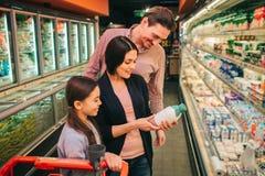 Unga föräldrar och dotter i livsmedelsbutik Kvinnahåll att mjölka flaskan och läsa ingredienser Fader- och dotterställning arkivbilder