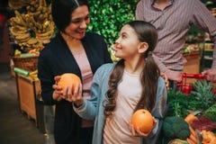 Unga föräldrar och dotter i livsmedelsbutik Liten flickablick på föräldrar och leendet Hon rymmer apelsiner i händer fader royaltyfri foto