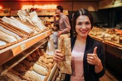 Unga föräldrar och dotter i livsmedelsbutik Positivt gladlynt kvinnahållbröd i händer och stor tumme för show upp Fathr arkivfoto