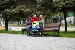 Unga föräldrar sitter på en bänk med hans unga son arkivfoto