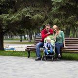 Unga föräldrar sitter på en bänk med hans unga son fotografering för bildbyråer