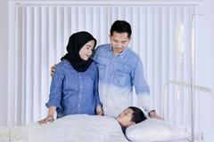 Unga föräldrar som besöker deras sjuka son i kliniken royaltyfri foto