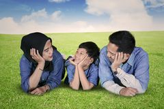 Unga föräldrar talar med deras son i ängen fotografering för bildbyråer