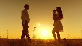 Unga föräldrar undervisar barnet att gå med deras fot i strålar av den guld- solnedgången