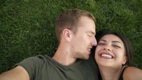 Unga förälskade heterosexuella caucasian par som utomhus vilar i, parkerar på gräsmatta, grönt gräs som ligger i omfamning, och f lager videofilmer