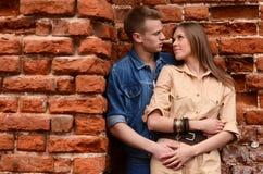 Unga förälskade par en tegelstenvägg Arkivbild