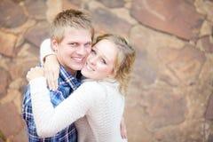 Unga förälskade vuxna par som ler, medan krama sig Royaltyfri Fotografi