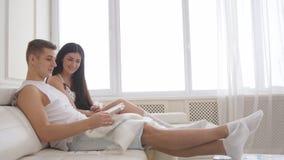 Unga familjpar - man och kvinna som tillsammans sitter på soffan och hemma spenderar tid arkivbild
