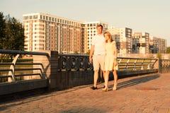 Unga familjpar som går och kramar i staden, parkerar nära floden fotografering för bildbyråer