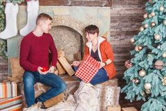 Unga familjpar som ser gåvor på spisen nära träd för nytt år fotografering för bildbyråer