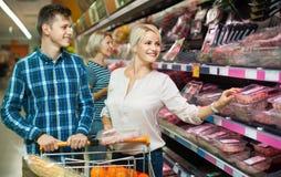 Unga familjpar som väljer kylt kött royaltyfria bilder