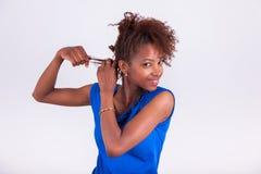 Unga flätade trådar för afrikansk amerikankvinnadanande till hennes burriga afro mummel Arkivbilder