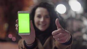 Unga flickan är den hållande smartphonen med den gröna skärmen och tummen upp på aftontid tillfällig livsstil arkivfilmer