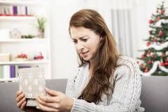 Unga flickan är olycklig om hennes julgåva Royaltyfria Bilder