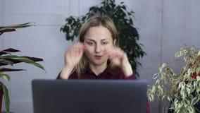 Unga flickan är under spänning, när han arbetar för en bärbar dator arkivfilmer