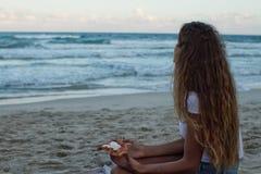 Unga flickan äter pizza på stranden, en matställe på stranden royaltyfri fotografi
