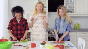 Unga flickan äter rågmellanmål under hennes nya sallad för vänkockar på köket lager videofilmer