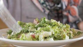 Unga flickan äter salat arkivfilmer