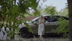 Unga flickan använder hennes telefon, under hennes pojkvänsammanträde på chaufförplats i bilen arkivfilmer