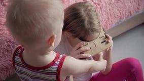 Unga flickan använder papp för virtuell verklighet VR, en apparat med, vilket kan erfara virtuell verklighet på en mobiltelefon lager videofilmer