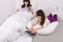 Unga flickan arbetar i sängen Fotografering för Bildbyråer