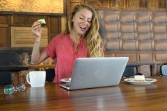 Unga flickan arbetar på datoren, och kakan, mat på datoren, en oskick äter Arkivfoton