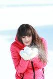 Unga flickan blåser av den vita snön med tumvanten Arkivbild