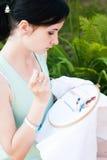 Unga flickan broderar en modell på det vita materialet Royaltyfria Bilder