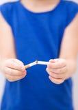 Unga flickan bryter en cigarett arkivbilder