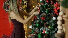 Unga flickan dekorerar julgranen lager videofilmer