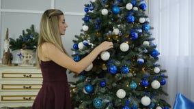 Unga flickan dekorerar julgranen stock video