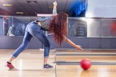 Unga flickan drar bollen på bowlingbanan Royaltyfri Bild
