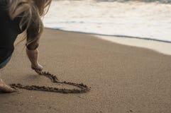Unga flickan drar en hjärta i sand som sitter på stranden Royaltyfri Fotografi