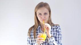 Unga flickan dricker orange fruktsaft till och med ett sugrör stock video