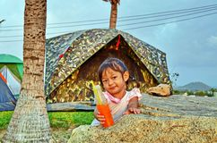 Unga flickan erbjuder hennes orange drink i en tältplats Royaltyfri Bild