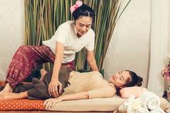 Unga flickan får thailändsk stilmassage av kvinnan för kroppterapi Arkivbild