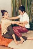 Unga flickan får thailändsk stilmassage av kvinnan för kroppterapi Arkivfoto