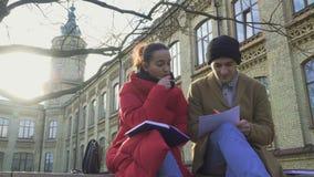 Unga flickan förklarar bildande material till hennes vän stock video