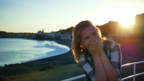 Unga flickan förvånas och skrattar ljust på stranden lager videofilmer