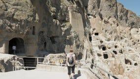 Unga flickan går i grottakloster Vardzia - Georgia arkivfilmer