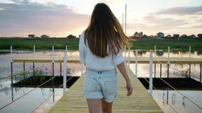Unga flickan går på träbron, sjön på solnedgången, följer skottet, ultrarapid lager videofilmer