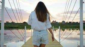 Unga flickan går på träbron, sjön på solnedgången, följer skottet, ultrarapid stock video