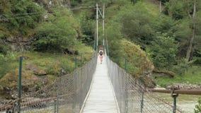 Unga flickan går på upphängningbron - Georgia arkivfilmer