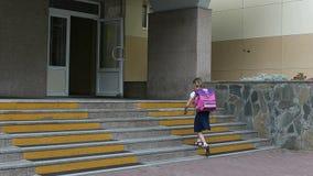 Unga flickan går till skolan som går vid trappuppgången, kommer in till skolaingången tillbaka begreppsskola till 1 september fli fotografering för bildbyråer
