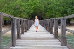 Unga flickan går vid träpir på havssandstranden royaltyfria bilder