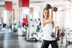 Unga flickan gör övningar med vikt i idrottshall arkivbild