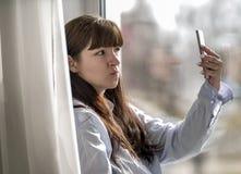 Unga flickan gör selfie, medan sitta vid fönstret arkivfoto