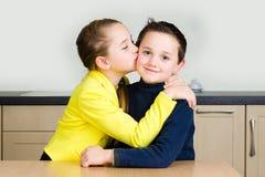 Unga flickan ger hennes broder en kyss Arkivfoton