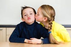 Unga flickan ger hennes broder en kyss Arkivbild